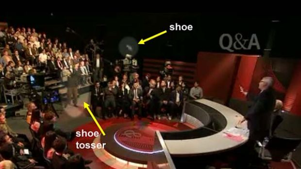 Hunter Valley man Peter Gray tosses his second shoe in the direction of John Howard as <i>Q&A</i> host Tony Jones stands ...