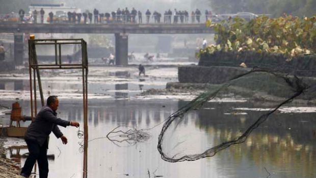 A fisherman casts his net into the muddy waters of a polluted canal in central Beijing.