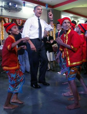 Getting into the local rhythm ... Barack Obama and Michelle Obama dance with children during a visit to the Holy Name ...
