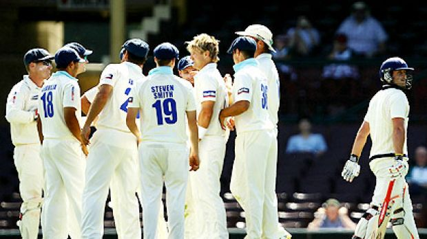 NSW teammates congratulate captain Shane Watson (without a cap) after taking the wicket of Michael Hill on the opening ...