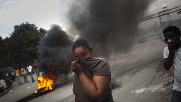 Violence spreads ...   smoke pours from tyres set alight by demonstrators in Port-au-Prince.