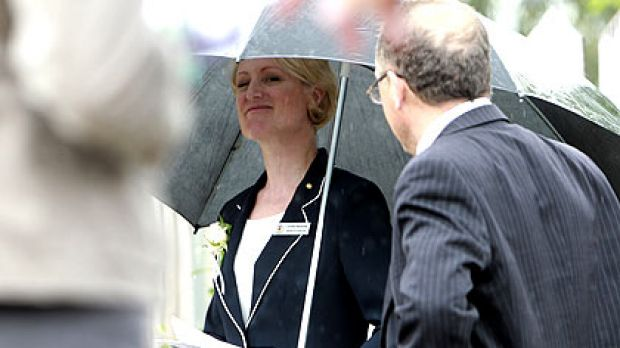 Former Olympian-turned-Labor politician Kirstie Marshall uses her personal minder and a large umbrella to dodge the ...