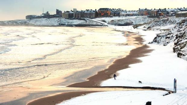 A man walks his dog on Tynemouth beach, north eastern England as Britain shivered in record low temperatures.