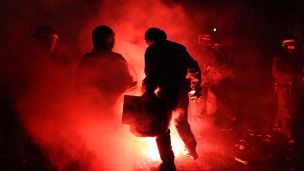 Violent protests ... a flare is thrown at police