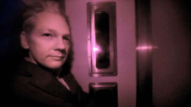 Julian Assange arrives in a police vehicle for his court appearance.