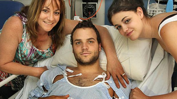 Blake Granston with his mother Michelle (left) and sister Emily (right) recovers in his hospital bed.