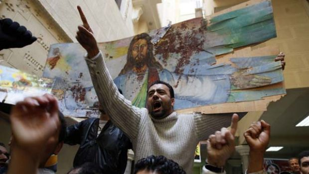 Tensions high ... Copts hold a bloodstained portrait of Jesus Christ at the Al-Qiddissine church, where 25 people were ...