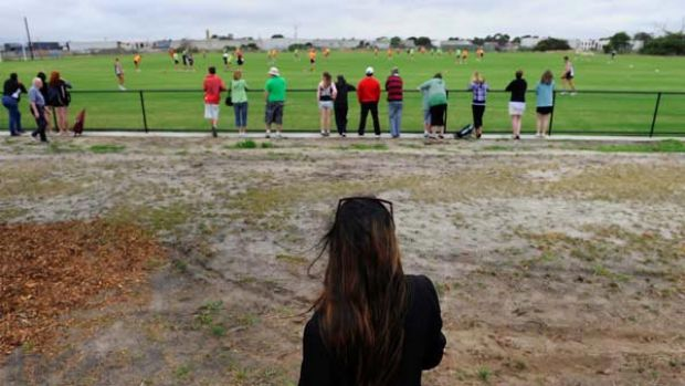 The teenager at the centre of the St Kilda scandal watches the team train today at Seaford.