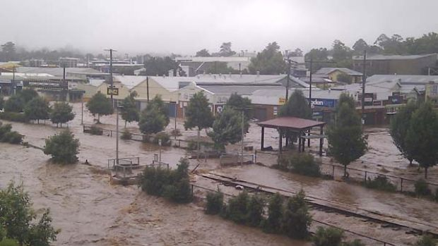 Wild scenes ... water pours through Toowoomba yesterday, picking up cars as if they were toys and inundating businesses.