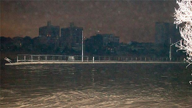 A large piece of the floating Riverwalk floats down the Brisbane River about 1am today. Photo: reader Conan Whitehouse