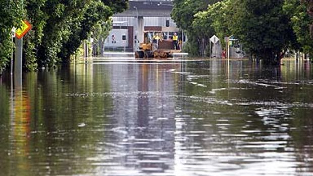 Workers ride in the bucket of a front end loader as its traverses flood water in the West End of Brisbane today.