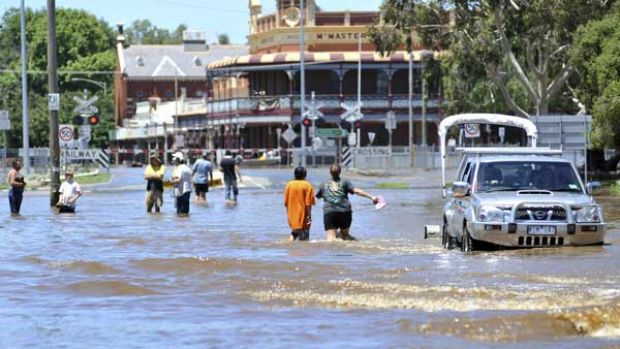 Residents wade through the main street of Rochester as the Campaspe River reached a record 9.15 metres yesterday ...