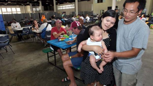 Sick ... Tri and Minh Hoang with their baby, Bau, who is being treated for a serious rash, at the Brisbane showgrounds.