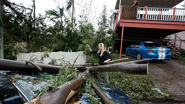 Inga Schlomm looks over the damaged remains of her friend's car in the wake of a massive storm which hit The Gap in 2008.
