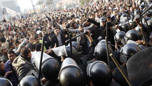 Anti-government protesters demonstrate near riot police at Tahrir Square in downtown Cairo.