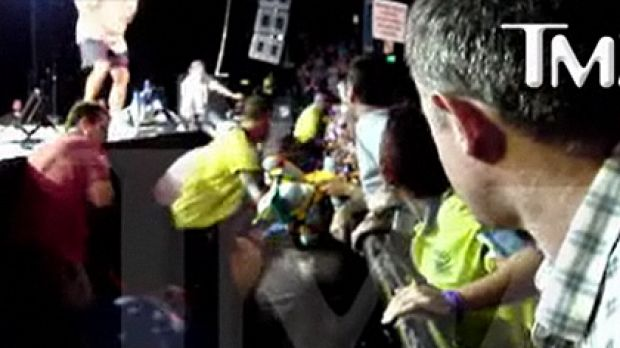Security can be seen rushing to Buffett's aid to screams from the crowd.