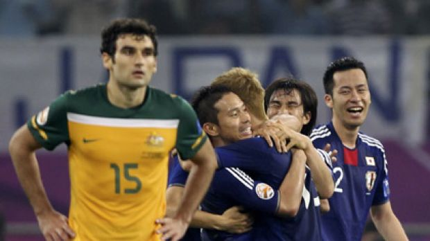 Japan players celebrate the winning goal as Australian midfielder Mile Jedinak ponders what might have been for the ...