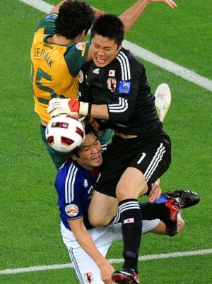 Japan's goalkeeper Eiji Kawashima and defender Daiki Iwamasa (bottom) challenge Australia's midfielder Mile Jedinak.