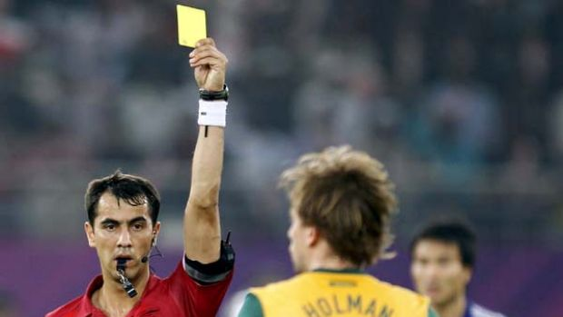 Referee Ravshan Irmatov of Uzbekistan shows the yellow card to Australia's Brett Holman.
