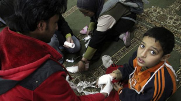 Wounded ... a doctor treats a child at a makeshift casualty ward in a Cairo mosque. There has been widespread use of ...