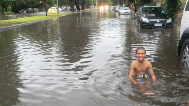 Flooding at the corner of Canterbury Road and Cowdery Street, St Kilda West: Mitchell Slavik, 11, has fun in the street ...