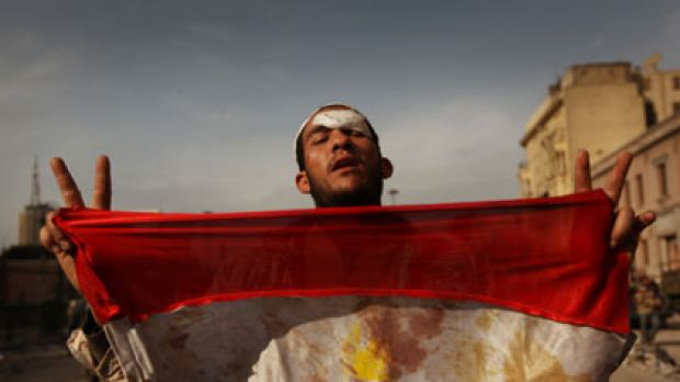 An anti-government demonstrator holds a bloodied Egyptian flag after a deadly battle with regime supporters in Tahrir ...