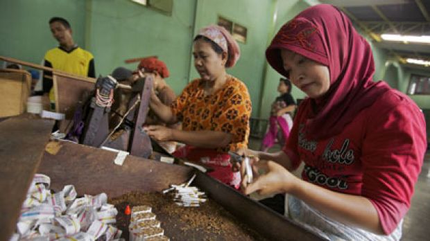 Hand made ... women work in pairs, rolling and cutting kretek cigarettes at a factory in Kudus. Each pair typically ...