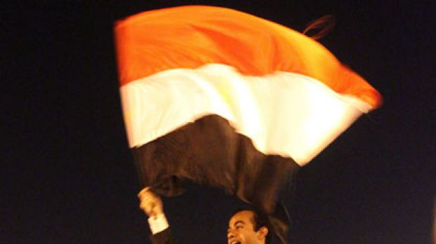 Flying the flag for change ... Abdullah al-Qadi waves the Egyptian flag while being carried by anti-government ...