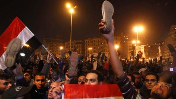 Angry ... protesters wave their shoes in disgust after President Hosni Mubarak's announcement.