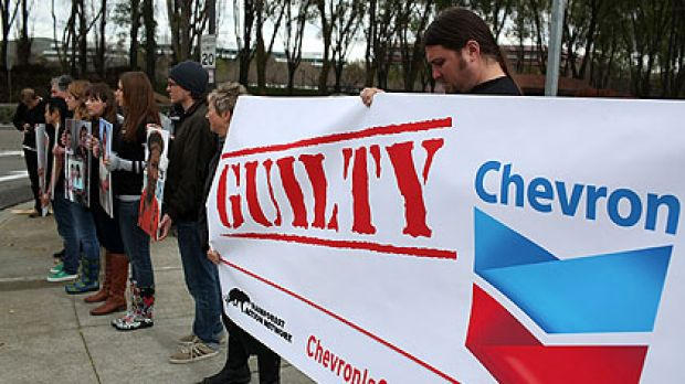 Protesters hold signs during a demonstration outside the Chevron headquarters in California.