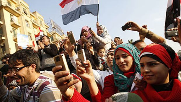 Young Egyptian men and women use their mobile phones to record the celebrations in Egypt's Tahrir Square at the ...