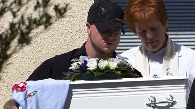 A man carries the casket of five-month-old Baxtor Gowland.