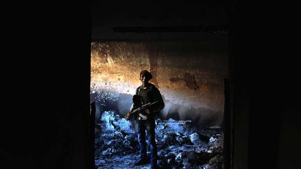 A rebel militiaman stands in the ashes of an alleged torture chamber of the former Libyan Internal Security force in ...