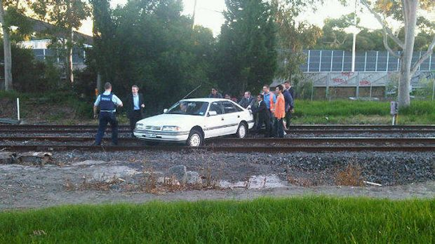 Attempts are made to push the car off tracks at East Malvern.