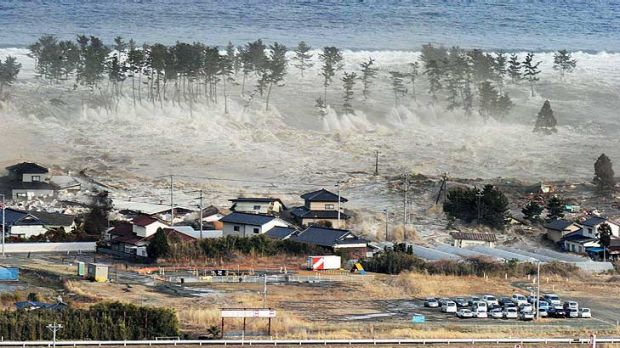 Waves from a tsunami hit residences after a powerful earthquake in Natori, Miyagi prefecture.