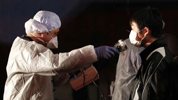 Official in protective gear scans for signs of radiation on a man who is from the evacuation area  near the Fukushima ...