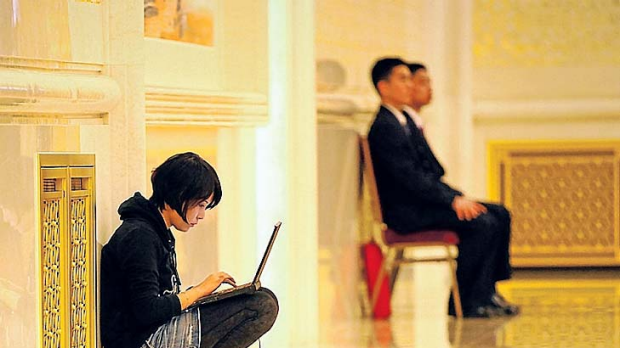 A reporter outside the Chinese Political Consultative Congress crouches with a computer to meet a deadline.