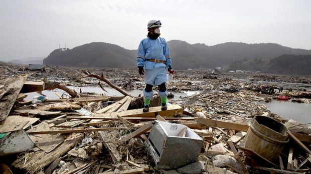 A rescue worker stands atop rubble during a body recovery mission in Ofunato.