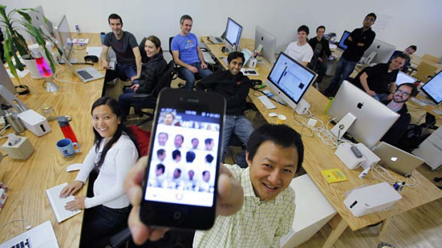 Color co-founder Bill Nguyen holds up his Apple iPhone with photos of himself using the Color application as he poses ...
