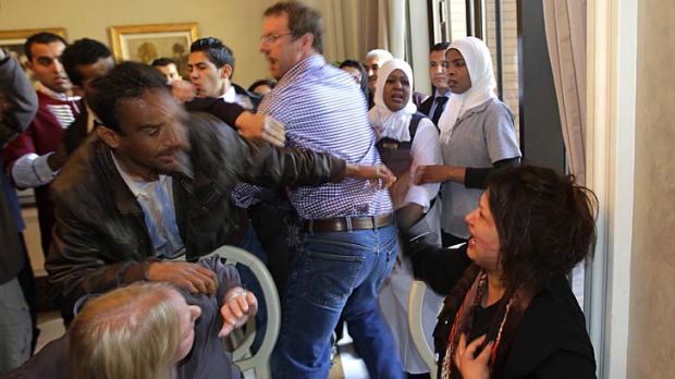 Desperate plea ... Ms Obeidi, centre, reacts as she is grabbed by a Libyan official, preventing members of the foreign ...