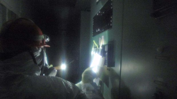 A picture released by Japanese Nuclear and Industrial Safety Agency  shows engineers at the central control room of the ...
