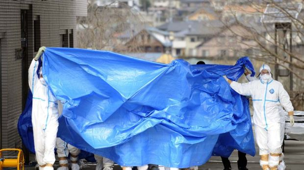 Workers who stepped into radiation-contaminated water at the Fukushima Dai-ichi nuclear plant are shielded with tarps ...