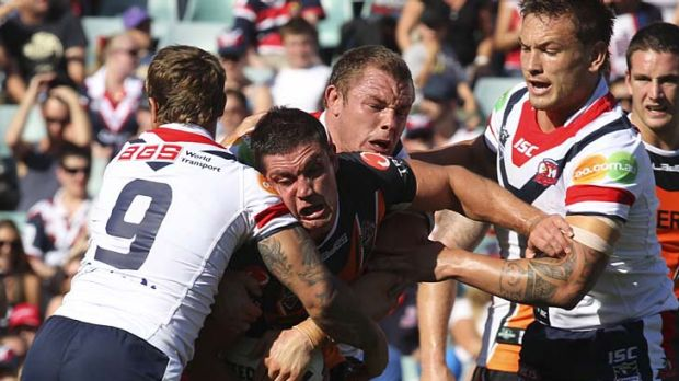Safety in numbers . . . Rooster Jake Friend, lft, gets plenty of help to tackle Wests Tigers forward Chris Heighington ...