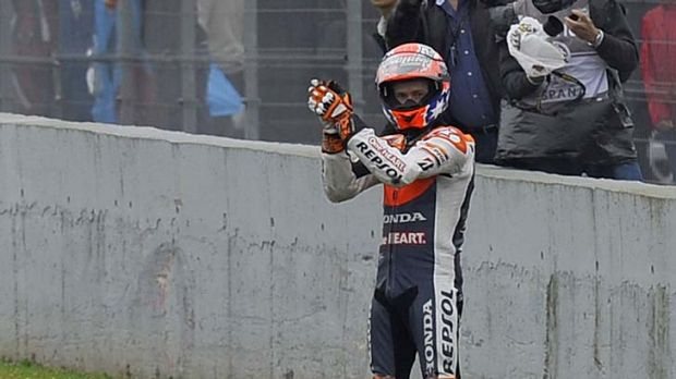 Casey Stoner gestures as Valentino Rossi rides away after their crash.