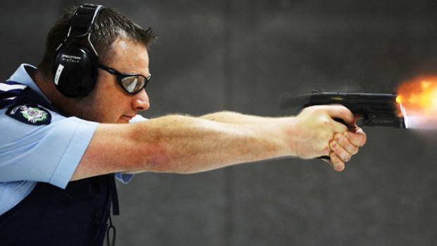 A Victoria Police officer tests the new Smith & Wesson. Protective services officers will receive about eight weeks' ...