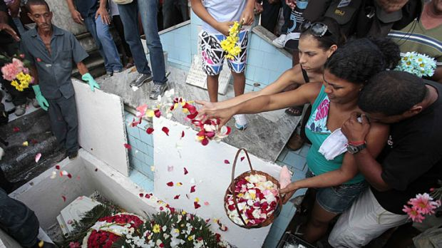 Tragic loss ... mourners sprinkle petals over the coffin of Gessica Pereira, who was 15.