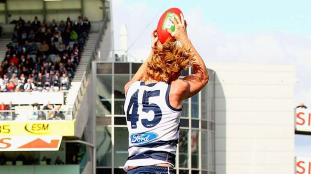 Above and below: Cats captain Cameron Ling crashes to the ground after flying for a mark over Steve Johnson.