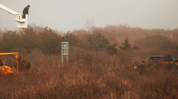 Police use a bucket lift to search for evidence after finding more remains.