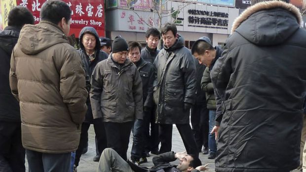 Unidentified men surround a foreign journalist in a Beijing shopping street in February in the aftermath of calls for a ...