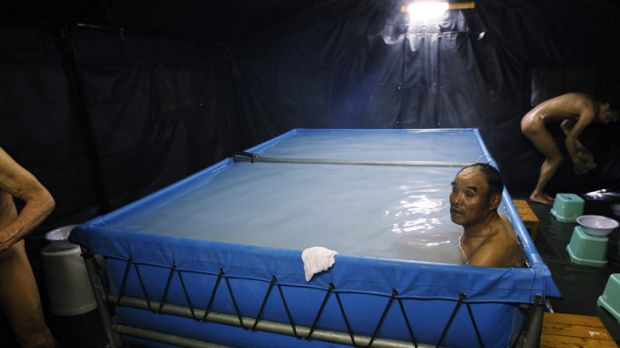 Men bathe at an evacuation centre  in Koriyama, Fukushima prefecture, Japan. Those who lived near the nuclear plant need ...